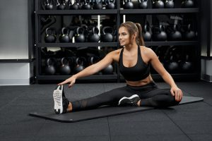 Side view of smiling woman in beautiful black sportswear doing stretching in modern gym. Concept of process stretching on mat after workout.